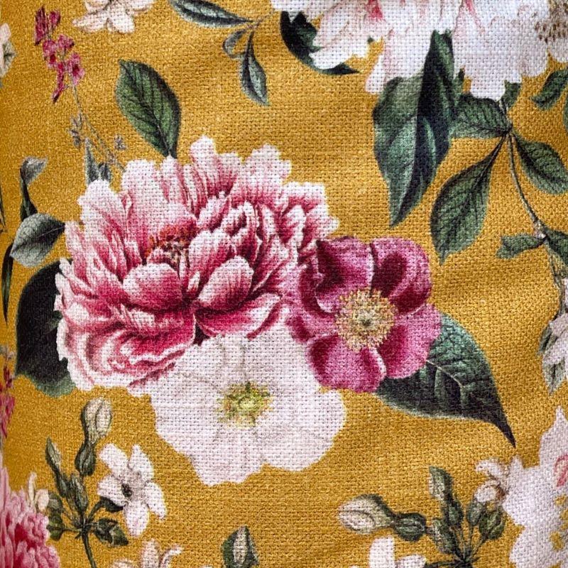 Detalle de la tela de algodón con diseño floral sobre fondo ocre